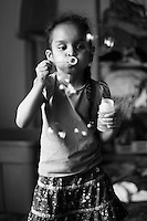 Young girl blowing bubbles in black and white