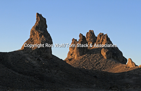 The Trona Pinnacles are tufa towers that formed underwater during the Pleistocene, when the area was covered by a much larger and deeper Searles Lake. The tufa, a form of calcium carbonate, was precipitated by the action of algae where calcium-rich spring waters entered the increasingly alkaline lake.  As Searles Lake shrank during drier Holocene time, the tufa towers have been exposed and subjected to erosion. The  pinnacles are similar to the younger tufa towers at Mono Lake. Trona Pinnacles National Natural Landmark. Near Trona, San Bernardino Co., Calif.