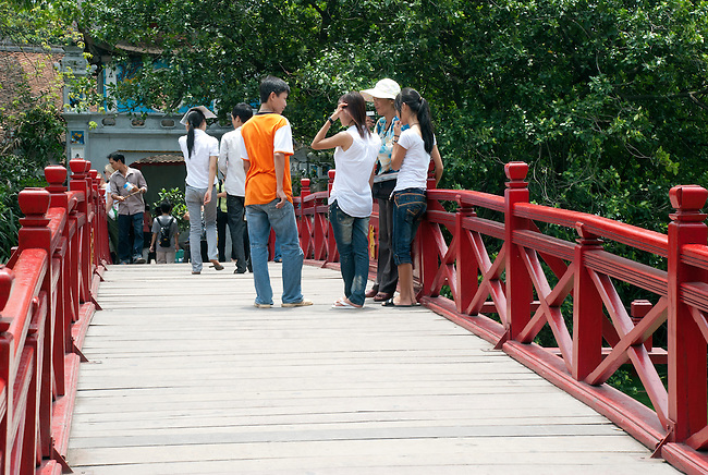 Hanoi, Vietnam, A young man meets girl friends and their mother on the bridge to Ngoc Son (Jade Mountain) Temple. photo taken July 2008.