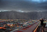 Apr. 26, 2011; Phoenix, AZ, USA; A dust storm converges on downtown Phoenix  haboob sandstorm dust monsoon storm chaser chasing city dusk Arizona man cameraphone cellphone urban