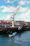 Crane hoisting fishing boat on to dock, Puerto de la Cruz, Tenerife, Canary Islands.
