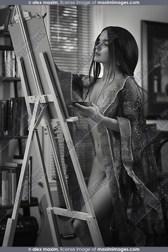 Beautiful young woman sumi-e artist with an easel painting naked in comfort of her home studio wearing a sheer robe. Artistic black and white portrait with retro feel.