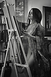 Beautiful young woman sumi-e artist with an easel painting naked in comfort of her home studio wearing a sheer robe. Artistic black and white portrait with retro feel. Image © MaximImages, License at https://www.maximimages.com