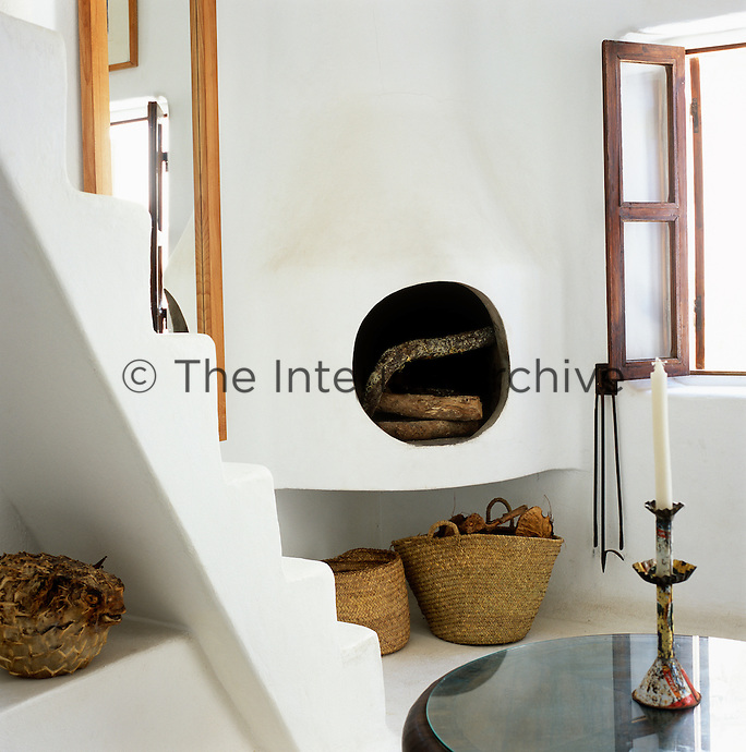 A wood burning stove built into the corner of the whitewashed living room