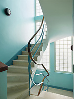 The apartment is reached by a winding staircase; the glass block wall allows plenty of light to flood into the entrance.