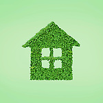Green home conceptual symbol made from green leaves. Isolated on green background.