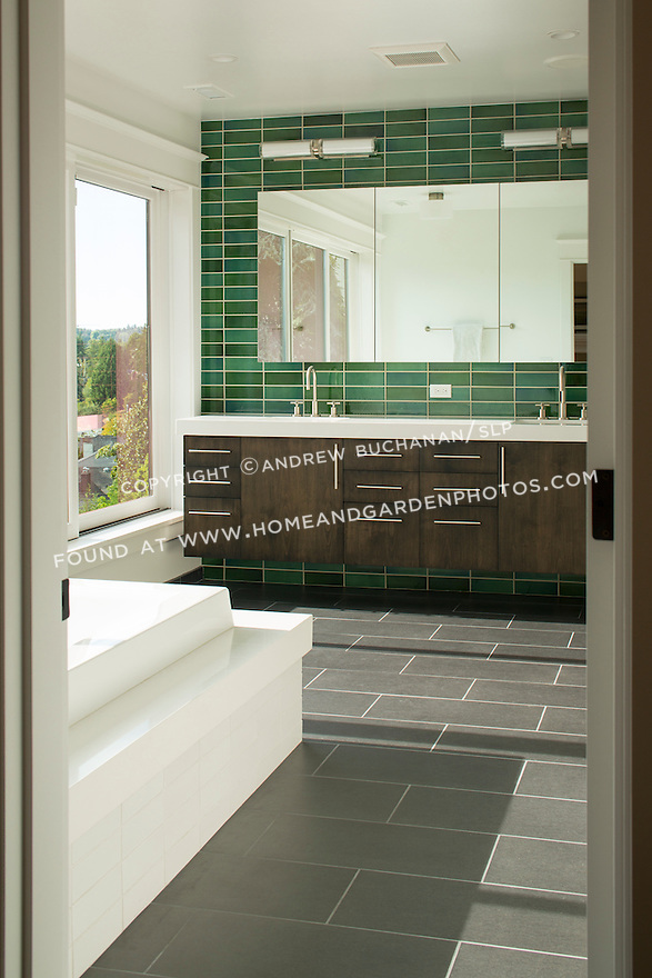 Bright green subway tiles line the wall behind a modern bathroom vanity. This image is available through an alternate architectural stock image agency, Collinstock located here: http://www.collinstock.com
