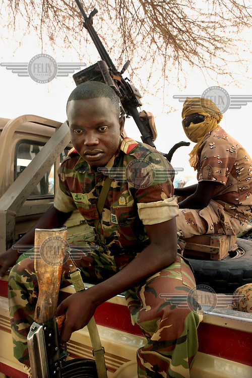 Nigerien soldiers guard members of the UNHCR at a camp for refugees in Mangaize, close to the Malian border. Niger has reportedly moved many soldiers into the area to prevent rebels from crossing the border.