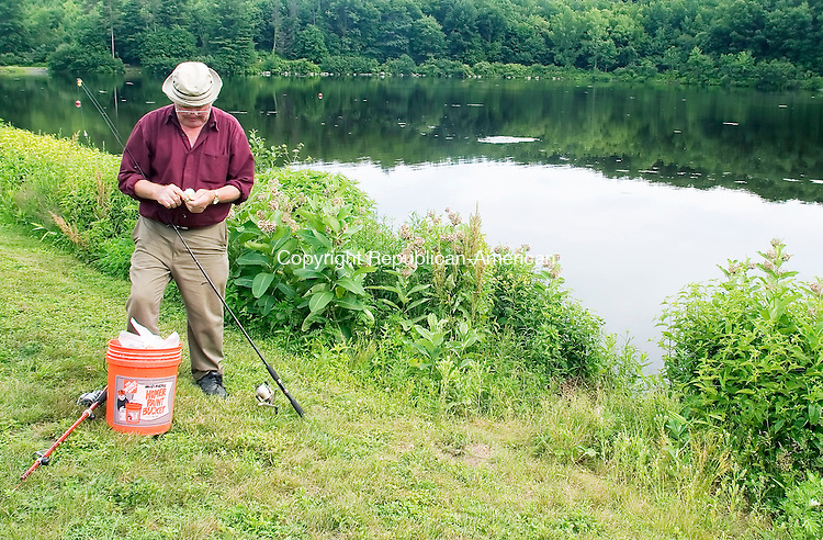 MIDDLEBURY, CT- 29 JUNE 2007- 062907JT04-<br /> Rocco Mancini of Waterbury prepares his fishing line at Hop Brook Lake in Middlebury on Friday evening. Though Mancini said it's hard to catch the good fish, he comes to the lake three to five times a week.<br /> Josalee Thrift Republican-American