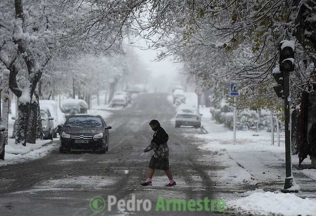 A woman walk under heavy snow, on December 14, 2009 in Aranjuez, near Madrid, during the first snow fall of the season. (c) Pedro ARMESTRE