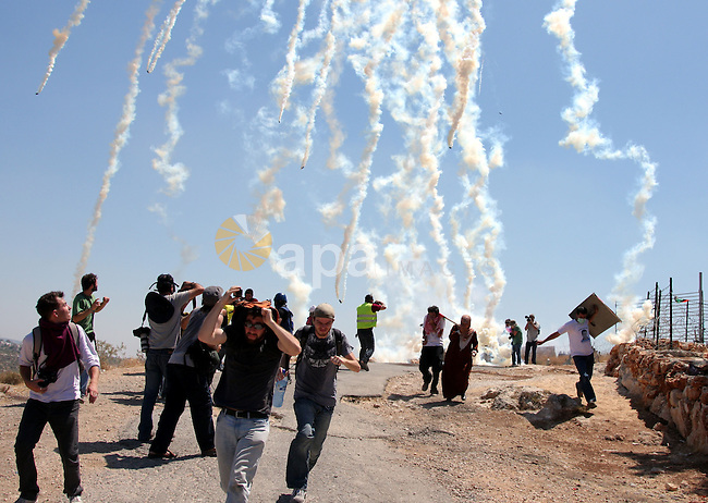 An Israeli soldiers fire tear gas against Palestinian and foreign protesters during a demonstration against Israel's controversial separation barrier in the West Bank village of Bilin near Ramallah on July3,2009. Photo by Issam Rimawi