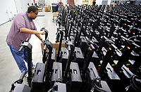 NWA Democrat-Gazette/DAVID GOTTSCHALK Julian Hendrickson, senior technician with Elections Systems and Software, moves Wednesday, March 28, 2018, an Express Vote ballot marking device kiosk into storage at the Benton County Election Commission in Rogers. Four hundred and seventy five devices and kiosk are being assembled for use in future elections.