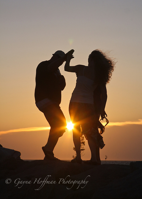 Man & woman in silhouette at sunset, doing a high five. Cape Cod, Rock Harbor, Orleans, MA