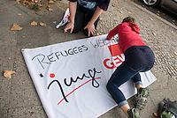 """Nach einer Woche Aufenthalt im Haus des Deutschen Gewerkschaftsbunds in Berlin liessen die Verantwortlichen des DGB etwa 25 Fluechtlinge durch die Polizei raeumen. Dabei gab es mehrere Verletzte, zwei davon nach Aussagen von Augenzeugen schwer. Mehrere Fluechtlinge wurden nach der gewaltsamen Raumung ins Krankenhaus gebracht. Mehrere Personen hatten sich zum Teil aneinander gekettet, um so die Raeumung zu verhindern.<br /> Die Fluechtlinge hatten vor einer Woche im DGB-Haus um Unterstuetzung fuer ihr Anliegen nach Asyl und Bleiberecht gesucht. Die Gewerkschaftsverantwortlichen waren jedoch nicht bereit ihnen mehr als ein paar Tage Obdach zu gewaehren und die Politik zu bitten das Problem zu loesen.<br /> Im Bild: Mitglieder der Gewerkschaft GEW beschreiben ein Gewerkschaftsfahne """"Refugees Welcome"""". <br /> 2.10.2014, Berlin<br /> Copyright: Christian-Ditsch.de<br /> [Inhaltsveraendernde Manipulation des Fotos nur nach ausdruecklicher Genehmigung des Fotografen. Vereinbarungen ueber Abtretung von Persoenlichkeitsrechten/Model Release der abgebildeten Person/Personen liegen nicht vor. NO MODEL RELEASE! Don't publish without copyright Christian-Ditsch.de, Veroeffentlichung nur mit Fotografennennung, sowie gegen Honorar, MwSt. und Beleg. Konto: I N G - D i B a, IBAN DE58500105175400192269, BIC INGDDEFFXXX, Kontakt: post@christian-ditsch.de<br /> Urhebervermerk wird gemaess Paragraph 13 UHG verlangt.]"""