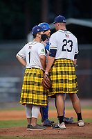 Savannah Bananas assistant coach Corey Pye (1) wears a protective mask for a mound visit with pitcher Joshua South (23) and catcher Bill Leroy (1) during a Collegiate Summer League game against the Macon Bacon on July 15, 2020 at Grayson Stadium in Savannah, Georgia.  Savannah wore kilts for their St. Patrick's Day in July promotion.  (Mike Janes/Four Seam Images)