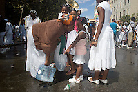 "Members of the United House of Prayer for All People, a non-denominational Pentecostal church in Harlem in New York on Sunday, August 3, 2008 collect water blessed by their bishop after a mass baptism. The church, which has held the baptisms on West 115 street since 1937, uses a fire hose to spray the congregation with city water blessed by the church's bishop. The ceremony is accompanied by music played by several brass ""shout"" bands. (© Frances M. Roberts)"