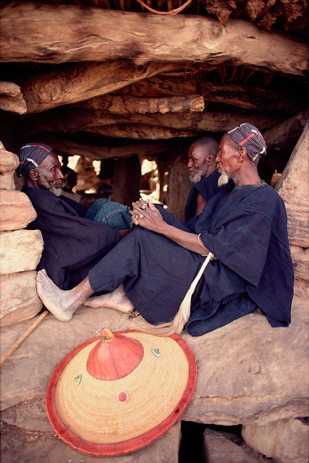 Dogon men sitting in the shade of the men's house, or Toguna. They wear indigo dyed clothing. Tireli. Mali. West Africa.