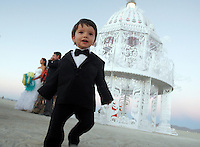 BLACK ROCK CITY, NV - AUGUST 27,2008:  A wedding in the desert. Sebastian, 18 months old wanders after his mothers wedding on the Playa. Mercedes Martinez and Chris Weitz held a wedding ceremony with friends gathered at Burning Man Event 2008. Participants from around the world converge in Nevada for the annual art event. The event, which culminates with the burning of large installation art over the weekend, attracts over 30,000 people annually.