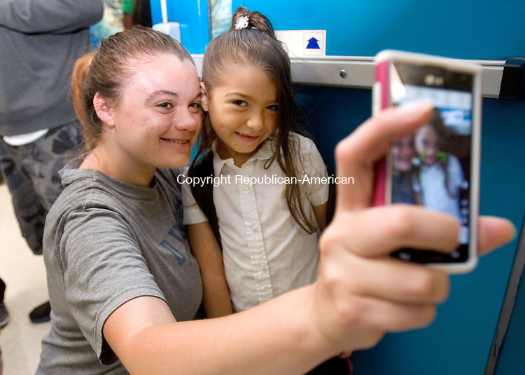 WATERBURY CT. 25 August 2014-082514SV01-Brittney Usher of Waterbury takes a picture of her and her daughter Nevaeh Usher, 6, while waiting to go to class at Driggs School in Waterbury Monday. Nevaeh was starting first grade. <br /> Steven Valenti Republican-American