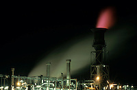 Illuminated chimney at a petroleum refinery, Berre, France.