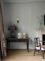 A marble-topped antique table stands in one corner of the dining room