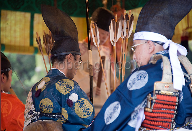 """A horse rider is given arrows that have been blessed during a ritual on the third day of the 3-day Reitaisai grand festival in Kamakura, Japan on  16 Sept. 2012.  The blessing service is held prior to the main attraction of the festival,the """"yabusame-shinji"""", where elegantly dressed mounted archers speeds down a 250-meter course and attempt to hit three wooden targets with their arrows. Photographer: Robert Gilhooly"""
