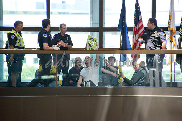 "United States Capitol Police prepare to arrest protestors chanting ""Healthcare is a right"" outside the office of United States Senator Lisa Murkowski (Republican of Alaska) in the Hart Senate Office Building in Washington, DC on Wednesday, June 28, 2017. Photo Credit: Ron Sachs/CNP/AdMedia"