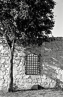 An iron window grate in a stone wall in Ragusa, Sicily, Italy..