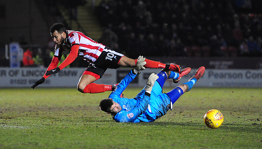 Cheltenham Town's Scott Flinders saves at the feet of Lincoln City's Matt Green<br /> <br /> Photographer Chris Vaughan/CameraSport<br /> <br /> The EFL Sky Bet League Two - Lincoln City v Cheltenham Town - Tuesday 13th February 2018 - Sincil Bank - Lincoln<br /> <br /> World Copyright © 2018 CameraSport. All rights reserved. 43 Linden Ave. Countesthorpe. Leicester. England. LE8 5PG - Tel: +44 (0) 116 277 4147 - admin@camerasport.com - www.camerasport.com