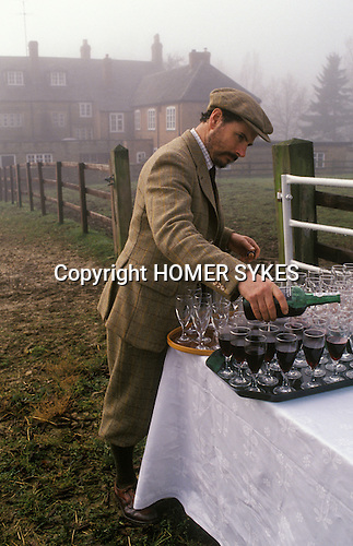 Fox hunting meet Heythrop Hunt, Oxfordshire, England. Hunt staff pouring the drinks , the stirrup  cup.