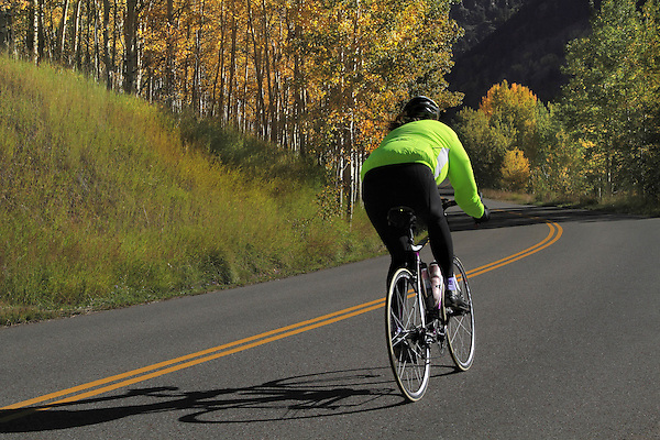 Person biking downhill on the Maroon Bells Creek Road with autumn Aspen trees, west of the town of Aspen, Colorado, USA John offers fall foliage photo tours throughout Colorado.
