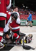 Matt Benning (NU - 5) helps Mike Gunn (NU - 6) with his skateguards. - The Northeastern University Huskies defeated the University of Massachusetts Lowell River Hawks 4-1 (EN) on Saturday, January 11, 2014, at Fenway Park in Boston, Massachusetts.
