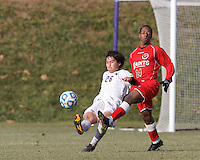 Amherst defender Justin Aoyama (26) clears the ball as St. Lawrence midfielder Ryan Grant (14) defends. NCAA Division III Sectionals. In double-overtime, Amherst College (white) defeated St. Lawrence University (red), 2-1, on Hitchcock Field at Amherst College on November 23, 2013.