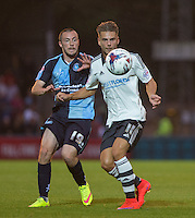 Alex Kacaniklic of Fulham holds off Michael Harriman of Wycombe Wanderers during the Capital One Cup match between Wycombe Wanderers and Fulham at Adams Park, High Wycombe, England on 11 August 2015. Photo by Andy Rowland.