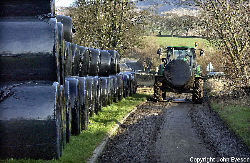 Colin Winterburn loading wrapped bales of straw at Red Lion Farm, Bolton Abbey, North Yorkshire ready for transport to Bob Turner's farm at nearby  Draughton. There were 1,400 bales of straw and haylage on the farm at the start of the winter. Some are sold and some used for  the farm's own suckler cows and store cattle.