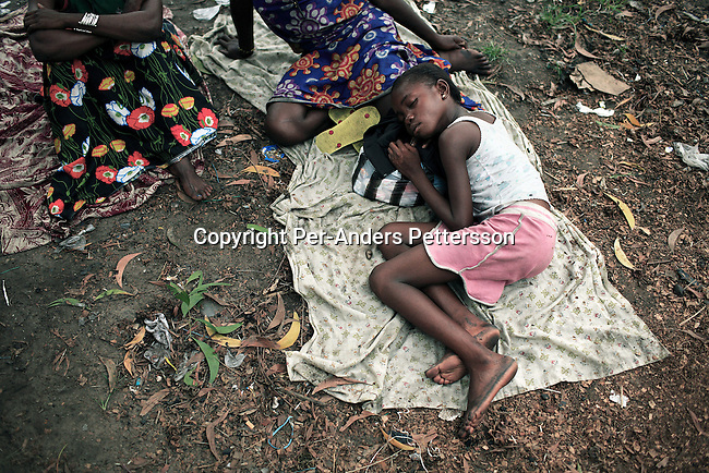 KINSHASA, DEMOCRATIC REPUBLIC OF CONGO APRIL 30: Esther Yandakwa, age 9, sleeps outside on the ground with her friends on April 30, 2006 in Matonge district in central Kinshasa Congo, DRC. Esther is homeless and works as a prostitute together with four fourteen-year-old friends. They live outside next to a polluted river. She's been three years on the street and has run away from here family. She has from time to time been living in a homeless shelter for children, but doesn't like the rules there. She usually smokes cigarettes, marijuana, drinks whiskey and sometimes takes Valium. She charges the clients as little as US$ 1. About 15,000 children are estimated to live on the streets of Kinshasa. Congo, DRC is in ruins after forty years of mismanagement by the corrupt dictator and former president Mobuto Sese Seko. He fled the country in 1997 and a civil war started. The country is planning to hold general elections by July 2006, the first democratic elections in forty years. (Photo by Per-Anders Pettersson).