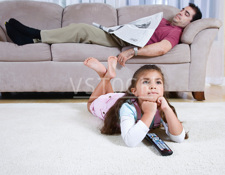 Girl (6-7) watching television, father with newspaper sleeping on sofa in background