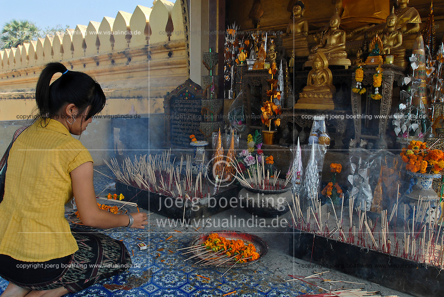 LAOS Vientiane, Buddha temple Pha That Luang the great Stupa, woman at prayer / Buddhistischer Tempel Pha That Luang , die grosse Stupa, vergoldete Buddha Statue