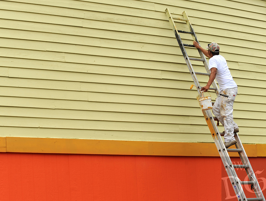 NWA Democrat-Gazette/ANDY SHUPE<br /> Jose Sanchez climbs a ladder Wednesday, July 5, 2017, while painting trim on the side of La Huerta Bar and Grill on South Thompson Street in Springdale. Sanchez was helping to spruce up the outside of the restaurant, which has been given a subtle color change and update.
