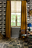 The geometric design of the black and white mural in the dining room creates an interesting contrast to the random pattern of flagstones on the floor