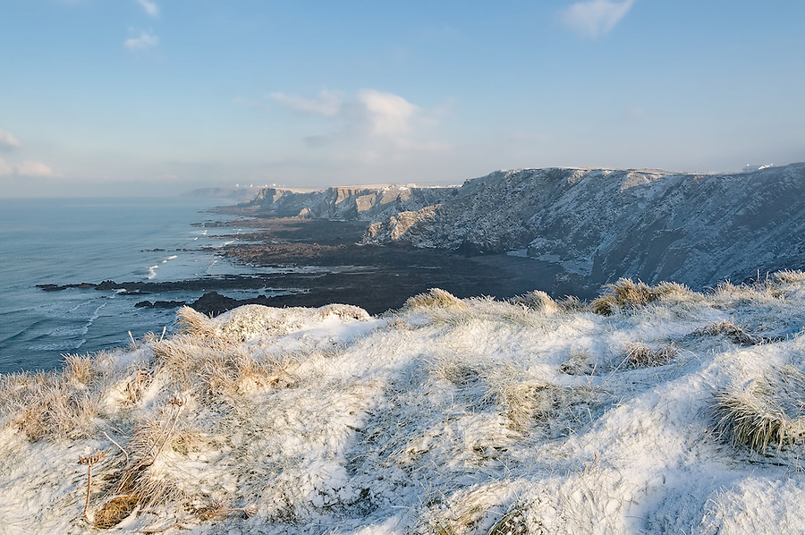 From Higher Longbeak this wintry view of the Culm Coast stretches north past Phillip's Point, the Upton Cliffs, Efford Down (with Bude hidden behind it), on to Menachurch Point and eventually to Lower Sharpnose Point with the satellite dishes of GCHQ Bude above it.
