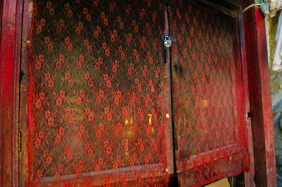 Red lace curtains covering door to offering altar at Chamba Gompa, along the Srinagar to Leh road. Mulbekh, Ladakh, India.