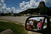 Tourists are reflected in a car mirror at Devil's Tower, an ancient volcano plug  or monolithic igneous intrusion that is more than 1200 feet high. It was featured in the Hollywood movie Closer Encounters of the Third Kind in 1977.