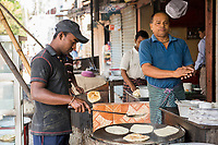 Bangladesh, Jhenaidah. Man making chapatis in the market.