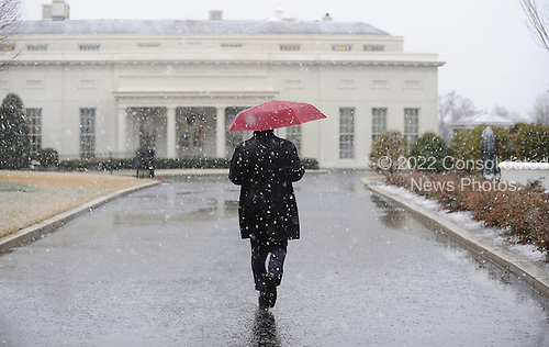 A White House staffer walks to the West Wing during a snow storm at the White House March 6, 2013 in Washington, DC. The snow forced all major school systems in the area to close, and cancelled today's White House press briefing..Credit: Olivier Douliery / Pool via CNP