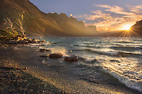 Fierce winds provoke crashing waves on the shore of St. Mary's Lake at sunset.