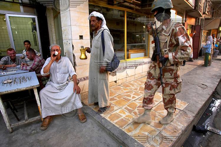 While drinking tea, a man eyes an Iraqi Army soldier on a training patrol with the US Army's Third Infantry Division 4-64 in Central Baghdad. In Baghdad's western Radwanya district, an Iraqi army soldier was killed and three were injured by a car bomb.