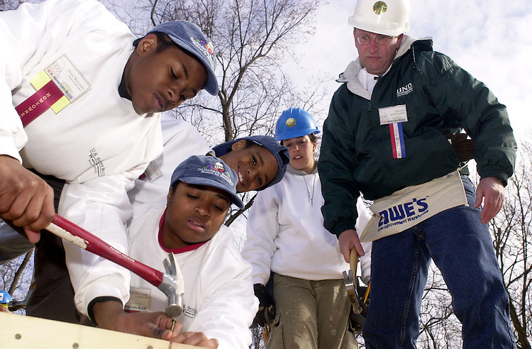 """24hfh030701 -- Sen. Kent Conrad, D-ND,  looks on as the Williams families works on their future home at a Habitat for Humanity event the""""U.S. Senators Build"""", in which Senators, from both sides, and their spouses worked on raising two house in Capitol Heights, MD."""