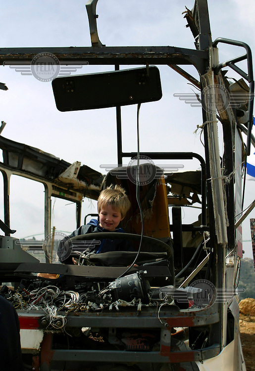 An Israeli boy sits in the driver's seat of a bus destroyed in a suicide bombing. The bus was placed by Israel?s Defense Ministry in the Jewish neighbourhood of Gilo, near the Palestinian West Bank village of Beit Jalla, as a reminder of the government's case for the erection of the controversial separation wall.