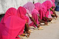 INDIA UP Bundelkhand, women movement Gulabi Gang, founded by Sampat Pal Devi, in pink sari fight for women rights and against violence of men, corruption and police arbitrariness, women receive lunch before protest rally in Mahoba / INDIEN Uttar Pradesh, Bundelkhand, Frauen unterer Kasten und kastenlose Frauen organisieren sich in der Frauenbewegung Gulabi Gang von Sampat Pal Devi , sie fordern gleiche Rechte und kaempfen notfalls mit Gewalt mit Bambusstoecken gegen gewalttaetige Maenner und korrupte Beamte, Frauen erhalten ein Essen vor der Demo in Mahoba